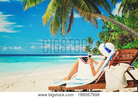 woman with touch pad drinking wine on tropical beach