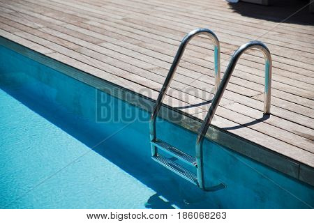 water sport and summer holidays concept - outdoor swimming pool ladder