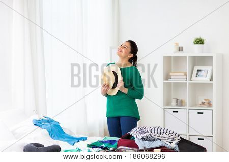 tourism, people and luggage concept - happy young woman with hat packing travel bag at home