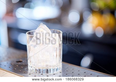 alcohol drinks and luxury concept - glass with ice cubes at cocktail bar