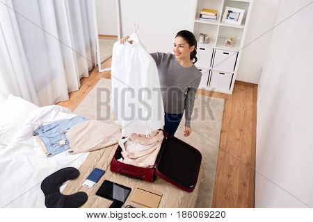 tourism, business trip, people and luggage concept - happy young woman packing travel bag at home or hotel room