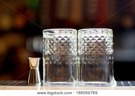 alcohol drinks, glassware and luxury concept - two vintage glasses and jigger on bar counter