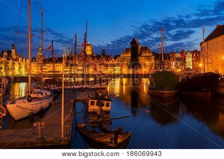 Night in Gdansk - old town waterfront with ships harbor illuminated in night, Gdansk, Poland