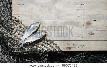 Dried and salty fish and fishing nets on the wooden background. Still-life and objects.