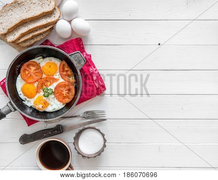 Eggs cooked overeasy with fried tomatoes and parsley, homemade bread, additional text space left, topview