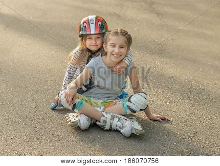 Two lovely sisters roller skating together, wearing protection, resting on the asphalt in park