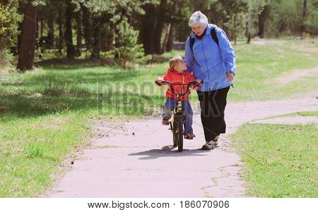 Grandmother teaching little granddaughter to ride bike in nature