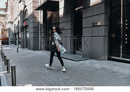 City girl. Full length rear view of young woman looking over her shoulder while walking down the street