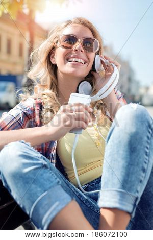 Young woman listening to music on a smart phone in the city.