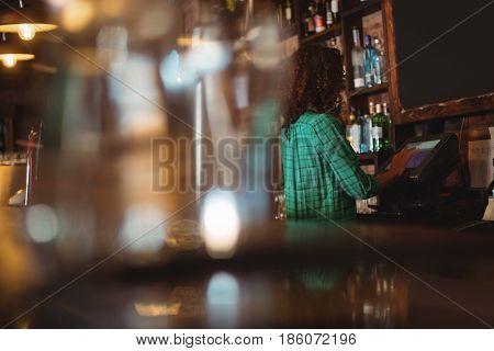 Female bar tender using electronic machine at bar counter