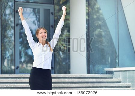 Celebrating businesswoman overlooking the city center. Business success. Happy businesswoman standing with hands up near building and smile