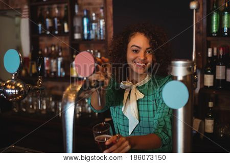 Portrait of waitress using beer tap at counter in pub