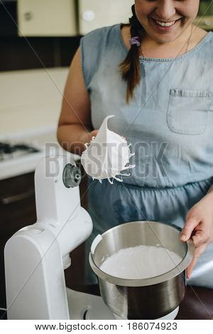 Young woman baking a cake using a mixer , mousee in the bowl