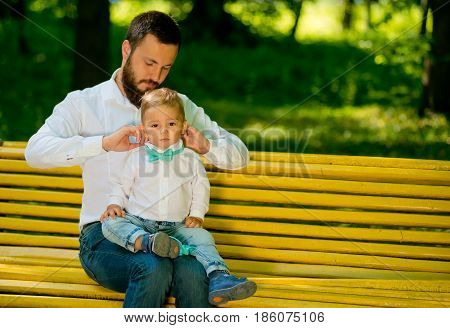 Little boy with his dad are trying on a bow tie They are sitting on a park bench. Father's day.