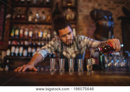 Waiter pouring tequila into shot glasses at counter in bar