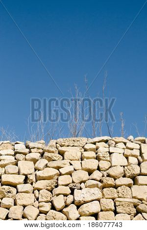 Abstract shot of sticks and grass in dry weather and rubble wall. Isolated typical elements of maltese countryside rural areas. Vertical portrait orientation.