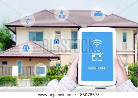 Hand using tablet with smart home control device on screen over blurred house background smart home concept