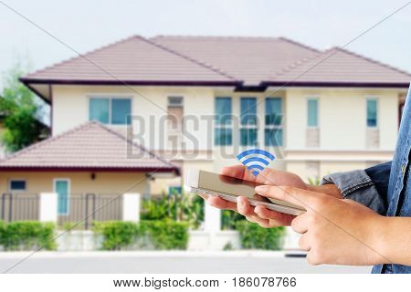 Hand using smart phone as smart home control application over blurred house background smart home concept