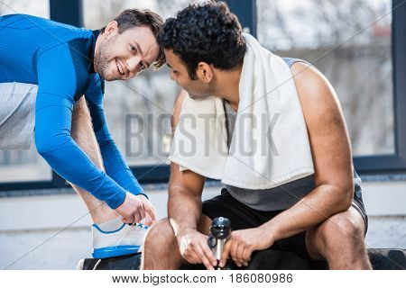 Handsome Young Man With Bottle Of Water Sitting On Tyre And Talking To Friend