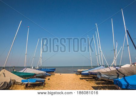 Small sailing boats lined up near the sea on the sand at Whitstable Kent United kingdom