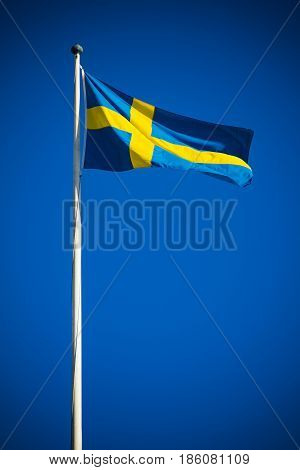 Sweden flag against clear blue sky in bright sunshine