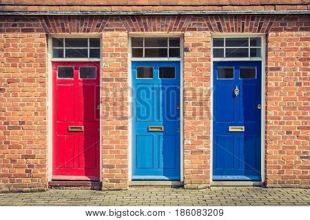 Three Differently Coloured Front Doors At The Entrance Of Old English Terraced Houses. Canterbury, E