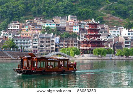 Zhenyuan, China - May 2, 2014: Tourists floating on the boat on Wuyang River in ancient town Zhenyuan of Guizhou Province.