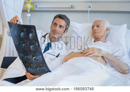 Senior doctor explaining xray to patient lying on hospital bed. Surgeon showing radiology report to old man admitted to hospital. Male doctor take care of his patient.