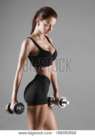 Nice sexy woman doing workout with dumbbells over gray background. Studio shoot.