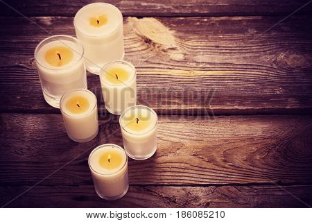 the scented candles on old wooden background