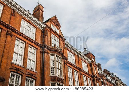 Old English brick houses in London United Kingdom. Diagonal line composition with blue sky and clouds.