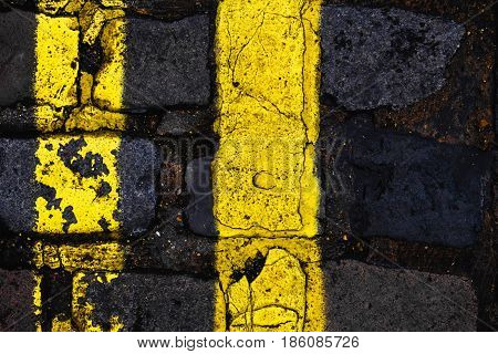Double yellow lines with cracked paint on a cobbled London street. vertical composition rule of thirds.
