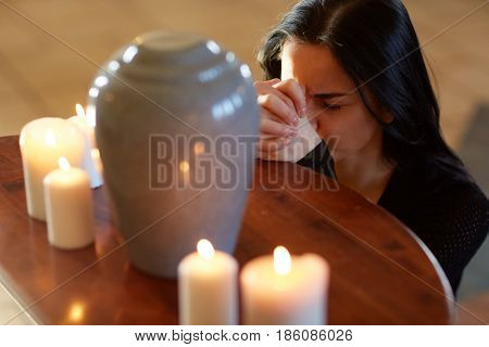 burial, people and mourning concept - sad woman with cinerary urn and candles praying at funeral in church