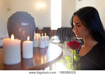 burial, people and mourning concept - sad woman with red rose and cinerary urn at funeral in church
