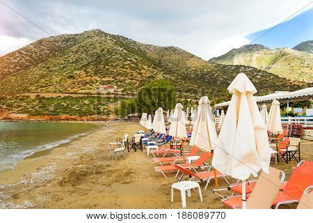 Sunny sandy Livadi beach in sea bay of resort village Bali in may. Views of mountain shore washed by waves and sun loungers with parasols where sunbathing tourists. Bali Rethymno Crete Greece