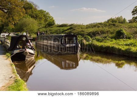 Chirk Wales UK - May 8 2017: A narrowboat passing moored up boats on a Summer evening on the Llangollen canal an idyllic getaway and alternative lifestyle on the waterway network