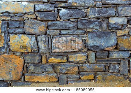 Stone texture of granite wall for creative background. Dark monolithic stones joined with cement in a single stone panel. Greek architecture Bali Crete