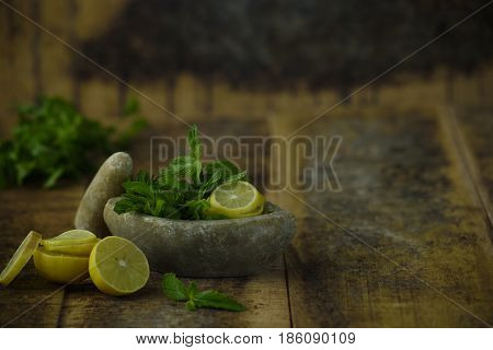 Lemon and mint. They are placed in the mortar pestle so that it can be crushed and later used as chutney or for juice. Its juice is good for detox.