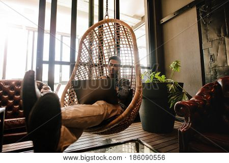 Male executive sitting on a wicker hanging chair in office lounge and looking at laptop. Man relaxing in office lounge working on laptop.
