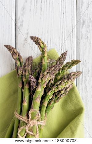 Fresh asparagus on wooden background, top view.
