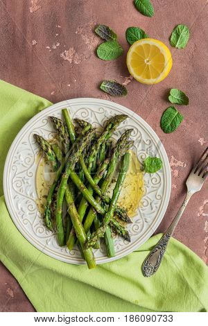 Baked asparagus with lemon and mint on concrete background, top view.
