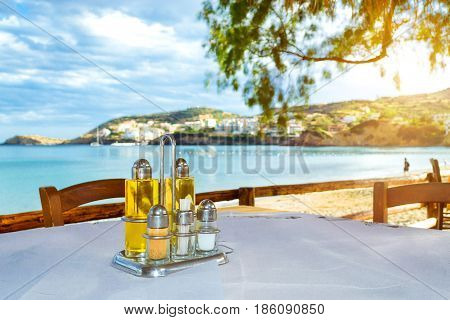 Cooking set olive oil salt pepper condiments and toothpicks are on table at beach cafe on the seafront. Livadi beach in sea bay of resort village Bali in may. Bali Crete Greece