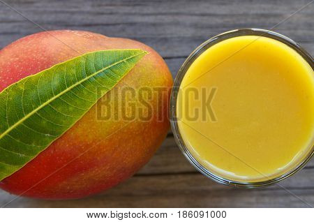 Fresh mango juice,ripe mango fruit and mango tree leaf on old wooden table background.Healthy food,diet or vegan food concept.Top view.