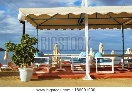 Tables with thatched umbrellas are on the road at beach cafe on the seafront. Livadi beach in sea bay of resort village Bali in may. Bali Crete Greece