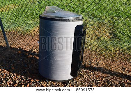 baseball field with grey garbage can pictured