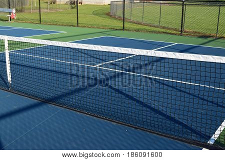 empty Pickleball playing ball court with net and blue courts