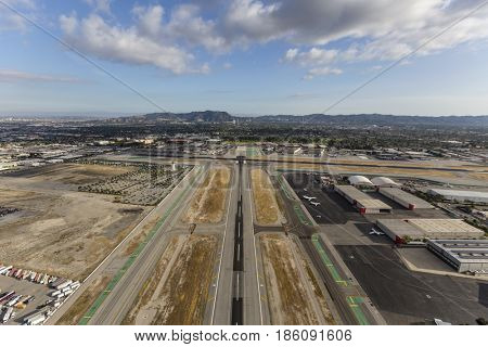 Burbank, California, USA - April 12, 2017:  Aerial view of airport runway with afternoon clouds in Southern California.