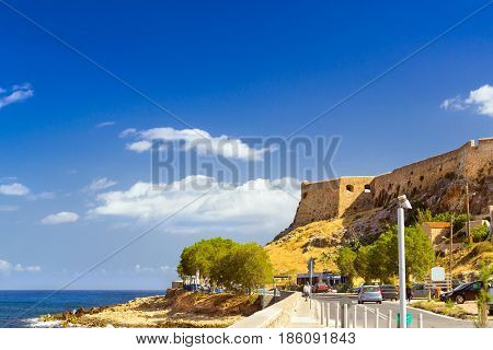 Fortezza Castle - Venetian fortress on hill Paleokastro in resort Rethymno. Greek architecture on coast of Kolpos Almirou. Highway along promenade Leof. Emmanouil Kefalogianni. Crete Greece