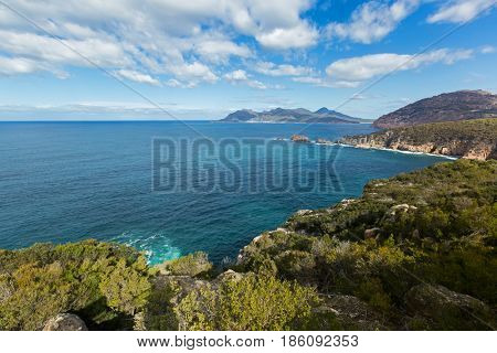 Turquoise waters of Carp bay, view from Cape Tourville Lighthouse lookout - Seascape photo, cliff coastline, green mountain, blue sky at Freycinet National Park, Tasmania, Australia