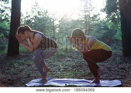Two girls meditating practicing yoga fitness exercise at sunset in forest. Padmasana